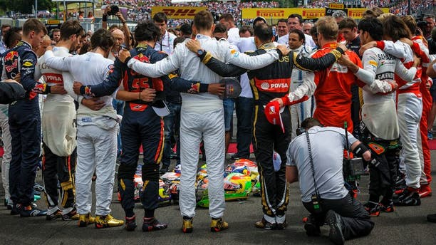 Forming a circle Formula One drivers embrace for a minute of silence to pay tribute to their recently deceased French colleague Jules Bianchi before the Formula One Hungarian Grand Prix on the Hungaroring circuit in Mogyorod, 23 km north east of Budapest, Hungary, Sunday, July 26, 2015. (Zsolt Czegledi/MTI via AP)