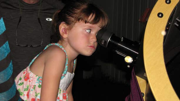 """July 28, 2015: Elizabeth """"Lizzy"""" Myers, 5, gazes through a telescope at the Warren Rupp Observatory in Bellville, Ohio."""
