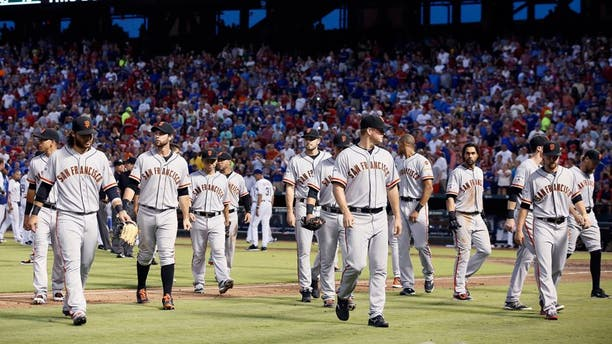 The San Francisco Giants return to their dugout after meeting the Texas Rangers on the field following a heated exchange between Giants pitcher Madison Bumgarner and members of the Rangers in the fourth inning of a baseball game Friday, July 31, 2015, in Arlington, Texas. (AP Photo/Tony Gutierrez)