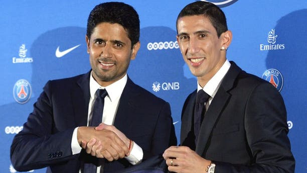 Paris Saint-Germain's (PSG) new Argentinian midfielder Angel Di Maria (R) and Paris Saint-Germain's Qatari president Nasser Al-Khelaifi (L) pose with Di Maria's PSG jersey during an official presentation in Paris on August 6, 2015. Paris Saint-Germain completed the signing of Di Maria from Manchester United on a four-year deal, the French champions announced. AFP PHOTO / MIGUEL MEDINA (Photo credit should read MIGUEL MEDINA/AFP/Getty Images)
