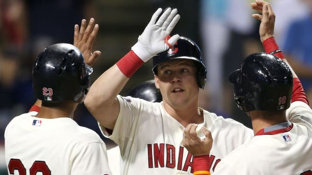Cleveland Indians' Jerry Sands, center, is congratulated from teammates Michael Brantley, left, and Yan Gomes after hitting a grand slam off Minnesota Twins relief pitcher Blaine Boyer during the fifth inning of a baseball game, Saturday, Aug. 8, 2015, in Cleveland.