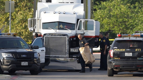 San Antonio police officers investigate the scene where eight people were found dead in a tractor-trailer loaded with at least 30 others outside a Walmart store in stifling summer heat in what police are calling a horrific human trafficking case, Sunday, July 23, 2017, in San Antonio