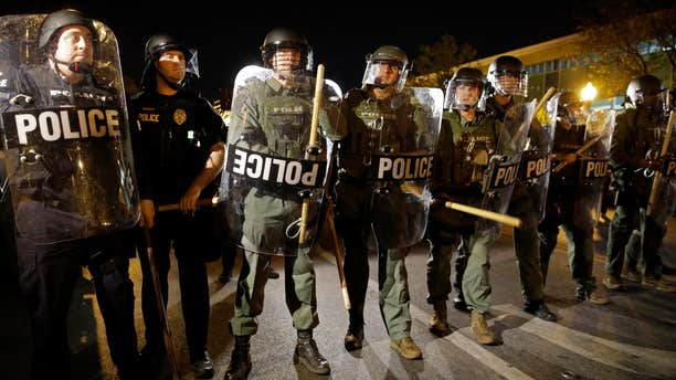 FILE - In this April 29, 2015 file photo, police stand in formation as a curfew approaches in Baltimore.