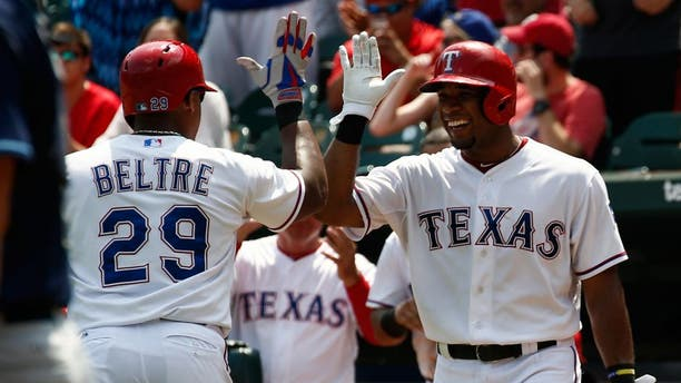 Aug 16, 2015; Arlington, TX, USA; Texas Rangers third baseman Adrian Beltre (29) is congratulated by shortstop Elvis Andrus (1) following his home run against the Tampa Bay Rays during the third inning of a baseball game at Globe Life Park in Arlington. Mandatory Credit: Jim Cowsert-USA TODAY Sports