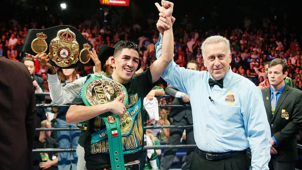 Leo Santa Cruz celebrates after he was announced the winner against Abner Mares in their WBC diamond featherweight and WBA featherweight championship boxing bout, Saturday, Aug. 29, 2015, in Los Angeles. (AP Photo/Danny Moloshok)