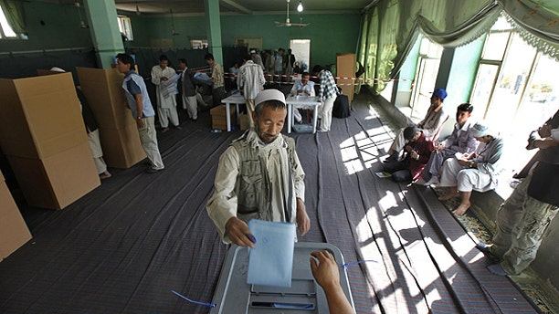 Sept. 18: An Afghan man casts his ballots at a polling station as agents of candidates, right, monitor the process in Kabul, Afghanistan, during the country's parliamentary elections.