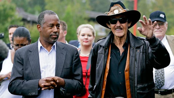 Republican presidential candidate, retired neurosurgeon Ben Carson listens to NASCAR legend Richard Petty during a tour of the Victory Junction Gang Camp in Randleman, N.C., Monday, Sept. 28, 2015. (AP Photo/Chuck Burton)
