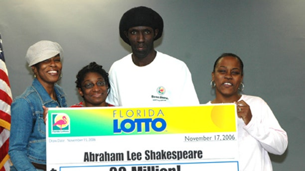 Abraham Shakespeare, center, displays an oversized check after winning the lottery in 2006. The last time anyone saw Shakespeare was in April.