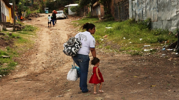 TEGUCIGALPA, HONDURAS - JULY 17:  A woman walks with her daughter in a gang infested neighborhood on July 17, 2012 in Tegucigalpa, Honduras. Honduras now has the highest per capita murder rate in the world and its capital city, Tegucigalpa, is plagued by violence, poverty, homelessness and sexual assaults. With an estimated 80% of the cocaine entering the United States now being trans-shipped through Honduras, the violence on the streets is a spillover from the ramped rise in narco-trafficking.  (Photo by Spencer Platt/Getty Images)