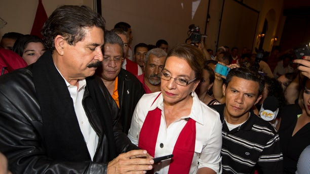 Free Party presidential candidate Xiomara Castro, center, and her husband, ousted President Manuel Zelaya, left, check information on his cell phone before the announcement of official election results in Tegucigalpa, Honduras, Sunday, Nov. 24, 2013. Hondurans cast ballots for a new president Sunday in a country reeling from violence, poverty and the legacy of a 2009 coup that ousted Zelaya. (AP Photo/Moises Castillo)