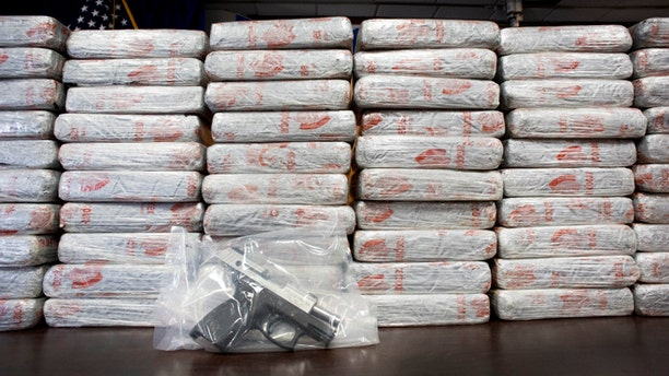 A firearm and 154 pounds of heroin worth at least $50 million are displayed by DEA, Tuesday, May 19, 2015 in New York.