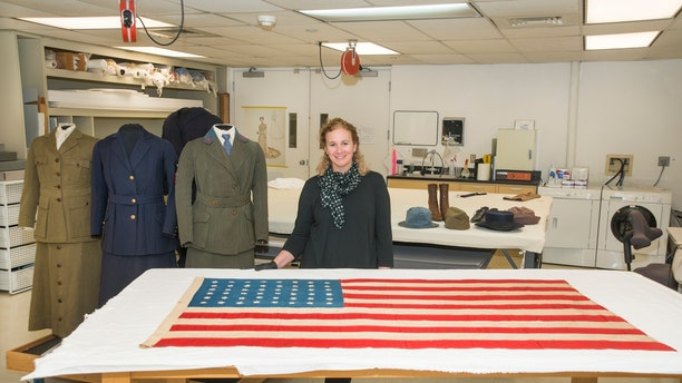 Curator Jennifer Jones  with WWI Islay Flag in the  Conservation Lab at the Nationl Museum of American History, Washington DC. See Centre Press story CPFLAG; A flag hand stitched on a Scottish island for a mass burial of American soldiers during World War I is making the 3,500-mile journey back to the island 100 years on. The stars and stripes were sewn in less than a day after the troopship SS Tuscania was struck by a German U-Boat around seven miles from Islay.