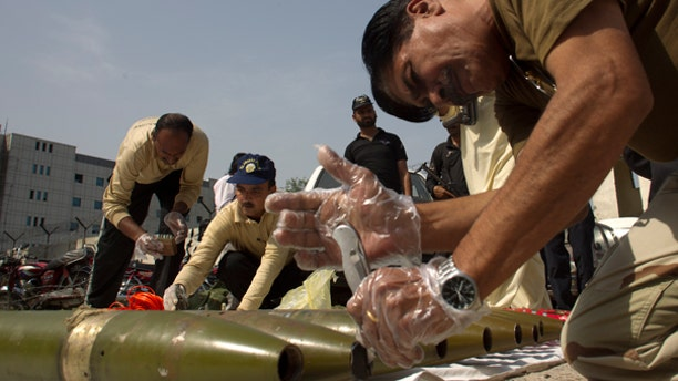 Oct. 8: Pakistani explosive experts defuse ammunition and suicide vests they recovered from a house in Islamabad, Pakistan.