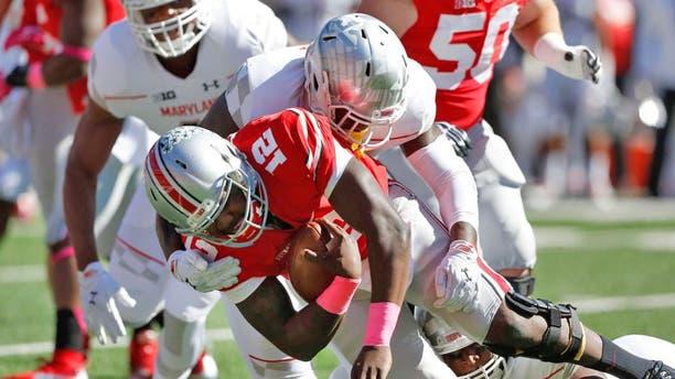 Oct 10, 2015; Columbus, OH, USA; Ohio State Buckeyes quarterback Cardale Jones (12) is sacked by Maryland Terrapins defensive lineman Yannick Ngakoue (7) during the first quarter at Ohio Stadium. Mandatory Credit: Joe Maiorana-USA TODAY Sports