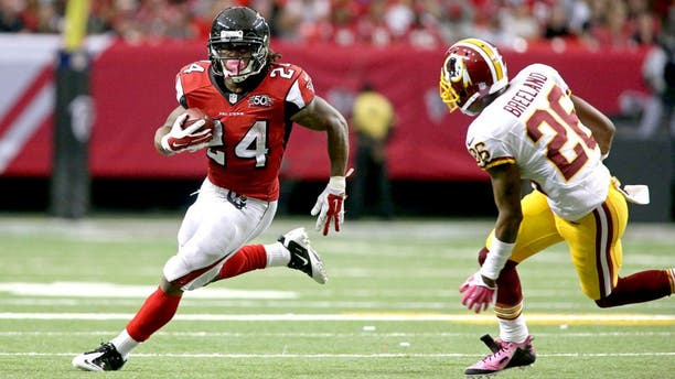 Oct 11, 2015; Atlanta, GA, USA; Atlanta Falcons running back Devonta Freeman (24) runs against Washington Redskins cornerback Bashaud Breeland (26) in the third quarter of their game at the Georgia Dome. The Falcons won 25-19 in overtime. Mandatory Credit: Jason Getz-USA TODAY Sports