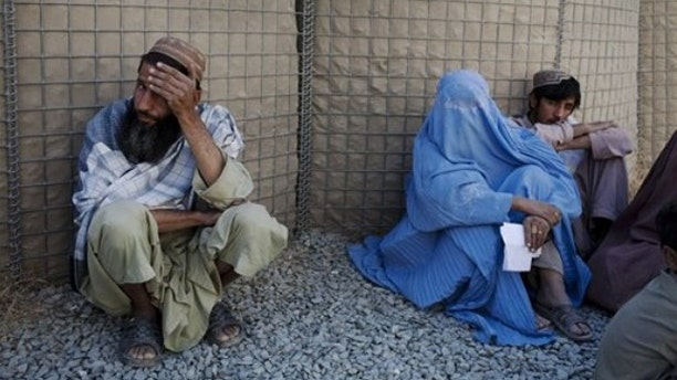Oct. 20: Afghans wait  to seek compensation for a relative's death outside Camp Nathan Smith, an ISAF military base in Kandahar City, Afghanistan.