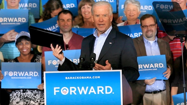Oct. 20, 2012: Vice President Joe Biden holds up a binder while remarking on Republican presidential candidate Mitt Romney's recent debate gaffe during a visit to Ketterlinus Gymnasium in St. Augustine, Fla.