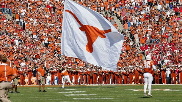 Oct 10, 2015; Dallas, TX, USA; Texas Longhorns cheerleader carries a Texas flag against the Oklahoma Sooners during Red River rivalry at Cotton Bowl Stadium. Mandatory Credit: Matthew Emmons-USA TODAY Sports