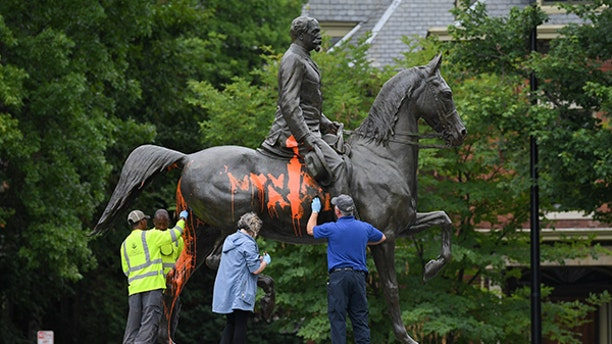 Municipal workers attempt to remove paint from a monument dedicated to Confederate soldier John B. Castleman that was vandalized late Saturday night in Louisville, Kentucky, U.S., August 14, 2017.  REUTERS/Bryan Woolston - RTS1BRYR