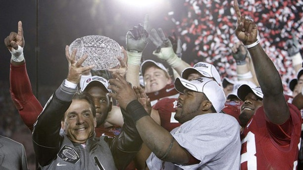 Jan. 7: Head coach Nick Saban (L) of the Alabama Crimson Tide and Heisman trophy winner Mark Ingram (R) hold the championship trophy after their team defeated the Texas Longhorns in the NCAA's BCS National Championship football game in Pasadena, Calif.