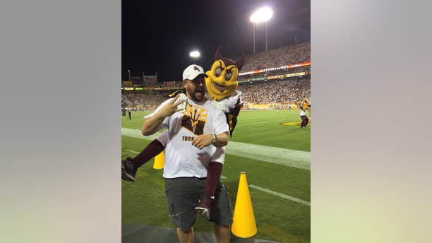 Sept. 18, 2015L This photo courtesy of David Schapira shows ASU's mascot Sparky jumping on David Schapira at a Arizona State University football game in Tempe, Ariz.