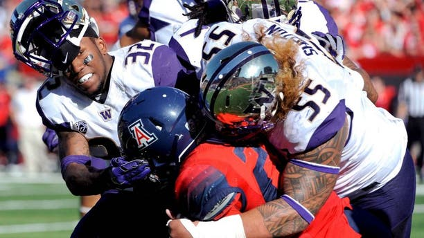 Nov 15, 2014; Tucson, AZ, USA; Washington Huskies defensive back Budda Baker (32) and defensive lineman Danny Shelton (55) tackle Arizona Wildcats running back Nick Wilson (28) during the first half at Arizona Stadium. Mandatory Credit: Casey Sapio-USA TODAY Sports