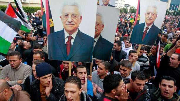 Nov. 25, 2012: Palestinians hold posters of Palestinian President Mahmoud Abbas during a rally supporting the Palestinian UN bid for observer state status, in the West Bank city of Ramallah.
