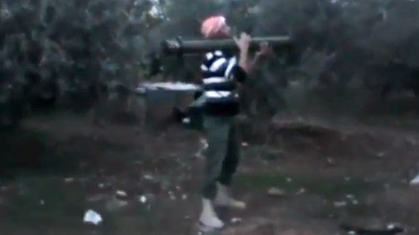 Nov. 27, 2012: In this image taken from video obtained from the Ugarit News, which has been authenticated based on its contents and other AP reporting, a Free Syrian Army fighter fires his weapon toward a military tank, unseen, in Daraa, Syria.