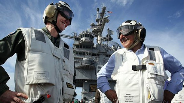 January 21, 2012: U.S. Defense Secretary Leon Panetta, right, escorted by the commander of Strike Group Twelve, Rear Adm. Walter E. Carter Jr., watches day flight operations from the flight deck of the aircraft carrier USS Enterprise.