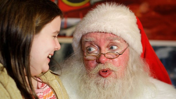 """John Toomey, the naughty Santa Claus who was fired from Macy's, visits with nine-year-old Retta Campbell of Sebastopol, Calif., on the first day of his new job in San Francisco, Friday, Dec. 10, 2010.  Toomey lost his 20-year job playing St. Nick at the Macy's downtown San Francisco store last weekend after an adult couple complained about a joke he made. He has since taken up a position playing Santa at Lefty O'Doul's, a nearby pub. Earlier this week he was on Jay Leno's """"Tonight Show."""" (AP Photo/Eric Risberg)"""