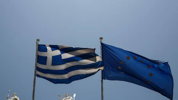 A Greek and a European Union flags flutter in front of statues of goddess Athena, left, and Nautilia, in front of Benaki museum in Athens, Greece, on Wednesday, June 17, 2015. Athens must pay 1.6 billion euros ($1.8 billion) off its debts at the end of the month to avoid a possible default and secure its cherished place among the 19 countries using the single currency.(AP Photo/Yorgos Karahalis)