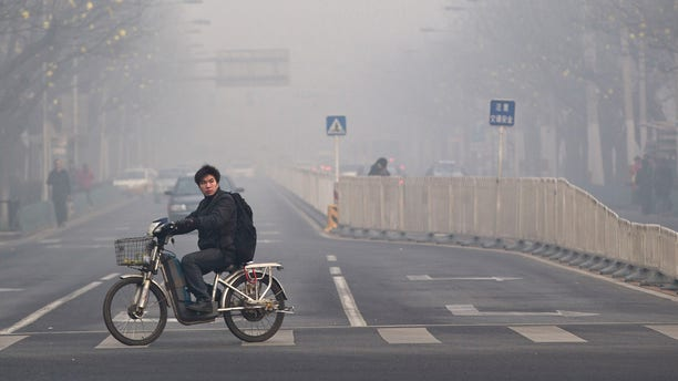 Jan. 10, 2012: A man rides an electric bike crossing a street shrouded by haze in Beijing. A senior Chinese environmental official told foreign embassies on Tuesday, June 5, 2012 to stop publishing their own reports on air quality in China, a clear reference to a popular U.S. Embassy Twitter feed that tracks pollution in smoggy Beijing.
