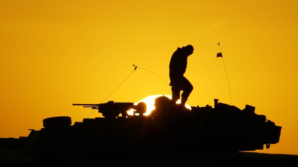 FILE - A U.S. soldier walks atop his armored vehicle at sunset as he prepares for a nighttime military exercise in the Kuwaiti desert south of the Iraqi border on Sunday, Dec. 22, 2002. Combat appears to have little or no influence on suicide rates among U.S. troops and veterans, according to a military study that challenges the conventional thinking about war's effects on the psyche published Tuesday, Aug. 6, 2013 in the Journal of the American Medical Association. (AP Photo/Anja Niedringhaus)