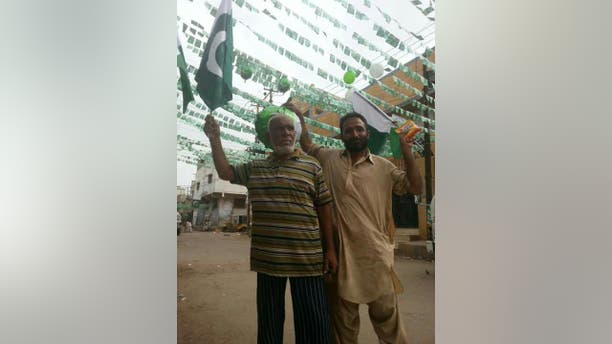 Locals in Lyari, Karachi, waving Pakistan flags.