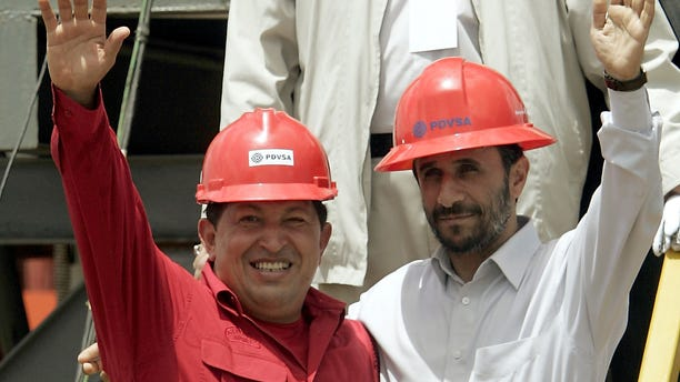 FILE - In this Sept. 18, 2006 file photo, Venezuela's President Hugo Chavez, left, and Iran's President Mahmoud Ahmadinejad wave to the press after inaugurating an oil drill in San Tome, Venezuela. Venezuela's Vice President Nicolas Maduro announced on Tuesday, March 5, 2013 that Chavez has died. Chavez, 58, was first diagnosed with cancer in June 2011. (AP Photo/Fernando Llano, File)