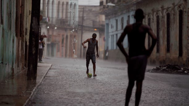 Two young men kick a soccer ball around in the rain on a flooded street in Havana, Cuba, Friday Sept.2, 2011.(AP Photo/Javier Galeano)
