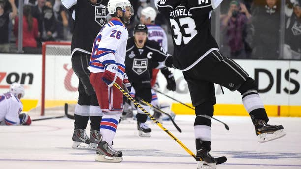 Los Angeles Kings right wing Dustin Brown, center, celebrates after scoring the game-winning goal, along with center Anze Kopitar, second from left, of Slovenia, and defenseman Willie Mitchell, right, as New York Rangers center Brad Richards, left, lies on the ice and Martin St. Louis (26) watches during the second overtime period in Game 2 of the NHL hockey Stanley Cup Finals, Saturday, June 7, 2014, in Los Angeles. The Kings won 5-4. (AP Photo/Mark J. Terrill)