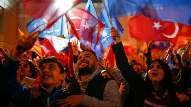 Supporters of Turkey's President Recep Tayyip Erdogan and The Justice and Development Party, (AKP), wave their party and national flags as they celebrates outside the AKP headquarters, in Istanbul, Sunday, Nov. 1, 2015.  Tens of millions of Turkish voters cast ballots in a contest that will determine whether the ruling party can restore the parliamentary majority it had enjoyed for over a decade. (AP Photo/Emrah Gurel)