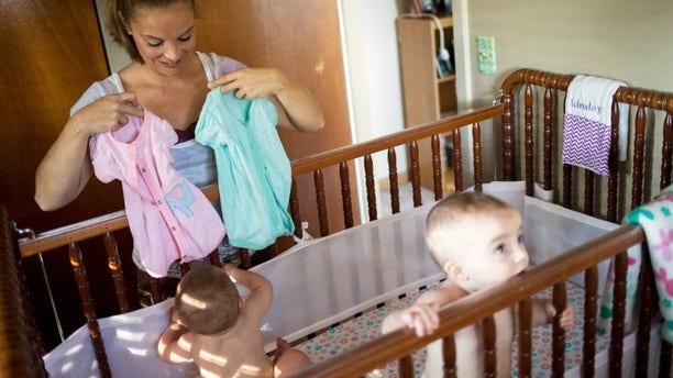 Heather Padgett dresses her daughters Kinsley and Kiley at her home in Cincinnati