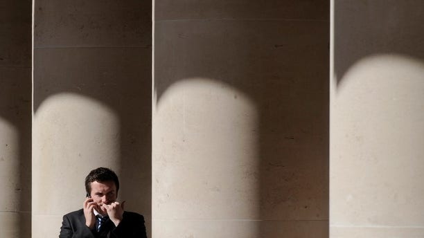 A city worker bites his nails outside the London Stock Exchange in Paternoster Square in the City of London