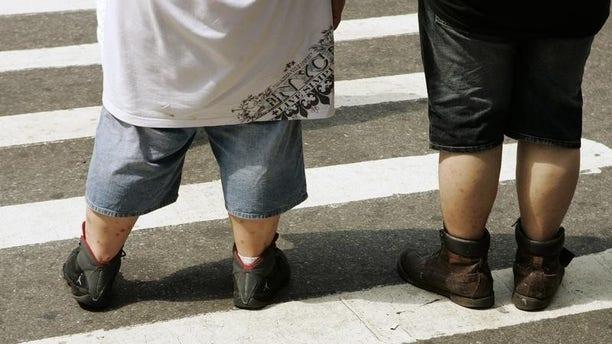 Pedestrians wait to walk across a street near Times Square in New York