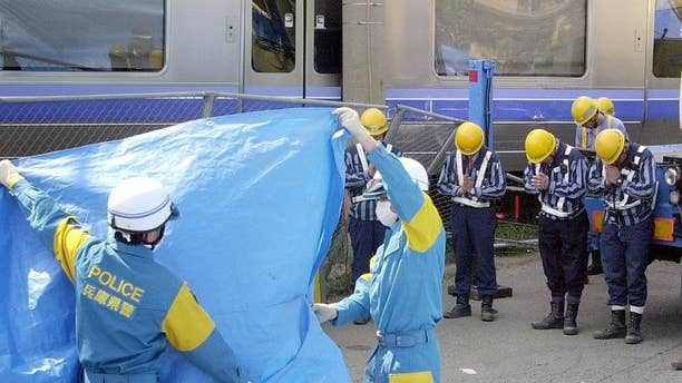 Japan Railway West (JR West) workers offer prayers to a dead body at the site of the train crash in Amagasaki in April 2005. Three former presidents of JR West have been cleared of responsibility for the 2005 train crash that killed over 100 people.