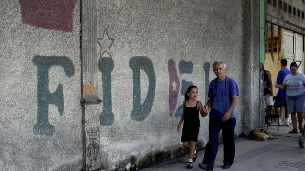 "HAVANA, CUBA - AUGUST 12:  A man walks in front of a wall that says ""Fidel"" August 12, 2003 in Old Havana, Cuba. Cuban President Fidel Castro turns 77 August 13, 2003 and has been in power for 44 years, making him the world's longest serving head of state. (Photo by Jorge Rey/Getty Images)"