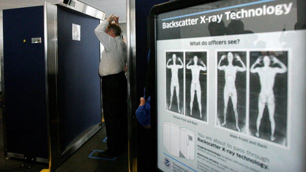 """In this photo taken Sept. 1, 2010, Transportation Security Administration employee Anthony Brock, left, demonstrates a new full-body scanner at San Diego's Lindbergh Field, with TSA employee Andres Lozano in San Diego. The American Civil Liberties Union has denounced the machines as a """"virtual strip search."""" Across the country, passengers must choose scans by full-body image detectors or probing pat-downs. Top federal security officials said Monday, Nov. 15, 2010, that the procedures were safe and necessary sacrifices to ward off terror attacks. (AP Photo/San Diego Union Tribune, Eduardo Contreras)"""