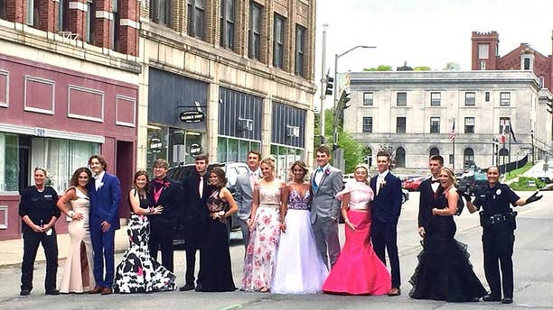 Two officers with Maine's Bangor Police Department posed for a prom photo with high school students after they were reported to police for blocking the street.