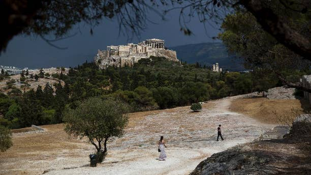 Tourist walk on Pnyx hill in front the ancient Acropolis hill, with the ruins of the fifth century BC Parthenon temple in Athens on Tuesday, June 7, 2016. Beginning as early as 507 BC, the Athenians gathered on the Pnyx to host their popular assemblies, thus making the hill one of the earliest and most important sites in the creation of democracy.(AP Photo/Petros Giannakouris)