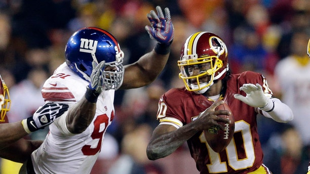 New York Giants defensive end Justin Tuck, left, tackles Washington Redskins quarterback Robert Griffin III (10) during the second half of an NFL football game Sunday, Dec. 1, 2013, in Landover, Md. (AP Photo/Patrick Semansky)