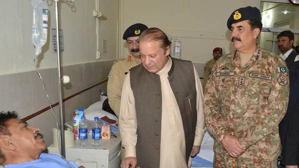 Pakistan's Prime Minister Nawaz Sharif talks to a survivor of the bombing with Pakistani army chief Gen. Raheel Sharif, right.