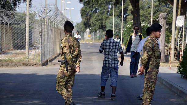 """In this photo taken on August 21, 2013 soldiers patrol the Isola di Capo Rizzuto migrant center, near Crotone, Southern Italy. Italian police on Monday, May 15, 2017 arrested 68 people, including a priest and the head of a Catholic volunteer group called """"Mercy,"""" accusing them of being in cahoots with a major mafia clan that skimmed millions in public funds destined for one of Italy's biggest migrant welcome centers. Investigators said the Arena clan of the Calabrian 'ndrangheta mob had secured a lock on servicing the Isola di Capo Rizzuto migrant center near Crotone for the past decade. (Francesco Arena/ANSA via AP)"""