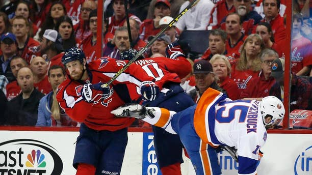 Washington Capitals center Brooks Laich (21), right wing Troy Brouwer (20) and New York Islanders right wing Cal Clutterbuck (15) collide during the first period of Game 5 in the first round of the NHL hockey Stanley Cup playoffs, Thursday, April 23, 2015, in Washington. (AP Photo/Alex Brandon)